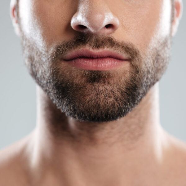 Cropped image of a half mans face with beard isolated over white background