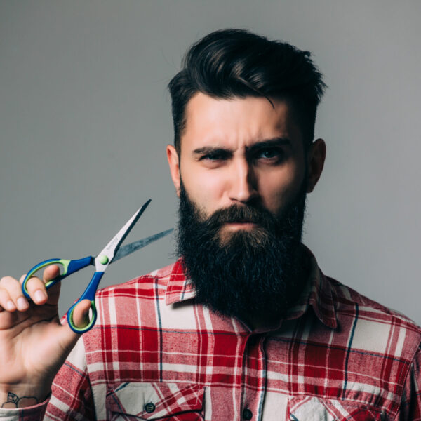 Handsome bearded man with long beard moustache and brunette hair holding hairdresser or barber scissors with emotional face in studio on grey background